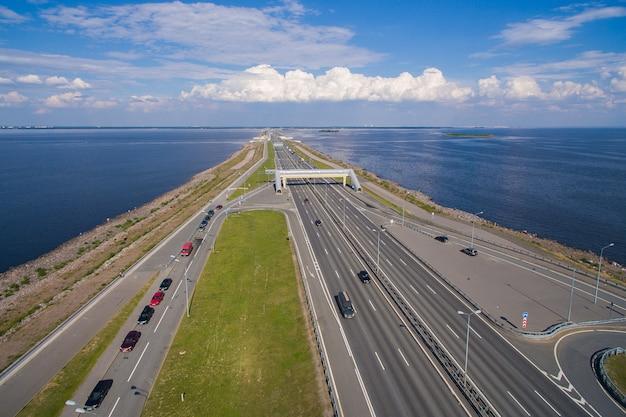 Аэрофотоснимок плотины в санкт-петербурге. она проходит через финский залив и соединяет города кронштадт и санкт-петербург. дамба движется транспортными средствами.