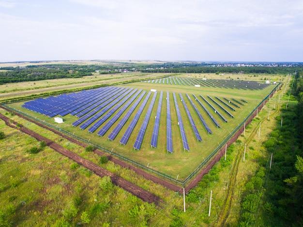 Панели солнечных батарей на зеленой траве с голубым небом.