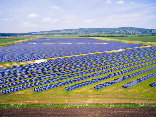 青い空と緑の芝生の上の太陽電池パネル。