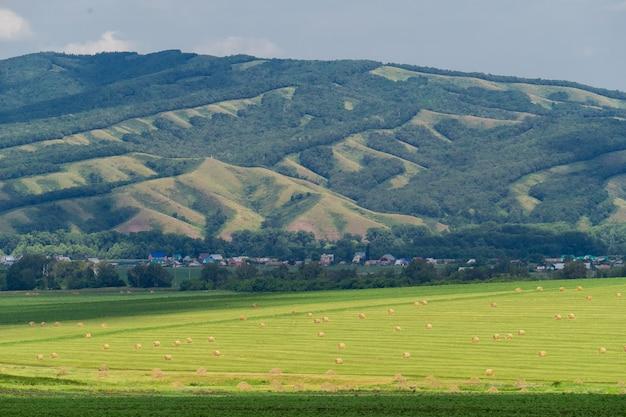 大きな丘に対して干し草の俵を持つフィールドの美しい風景。