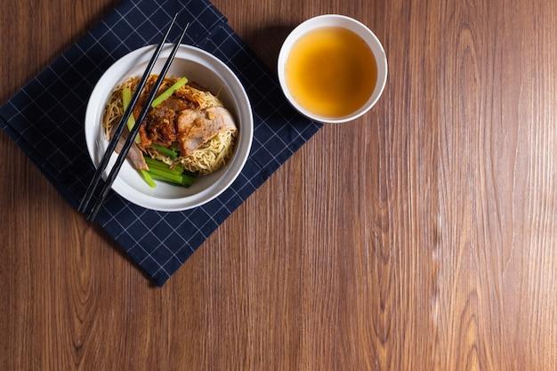 豚ワンタン麺のスープ、木製のテーブル