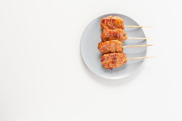 タイ風串焼きプレートの上に置かれた豚肉はタイの屋台の食べ物