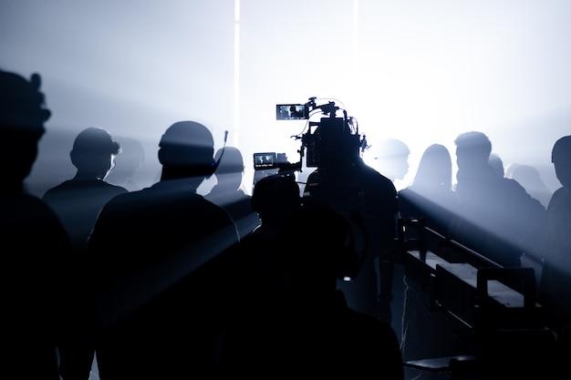 Съемочная студия за кадром в силуэтных кадрах, которые съемочная группа работает для кино или видео