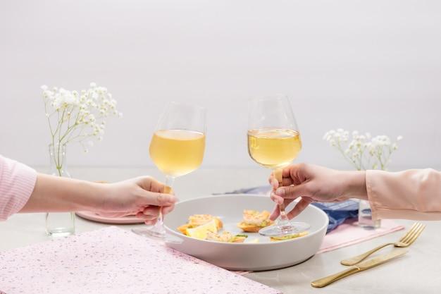 おいしいワインのロマンチックなディナーと素晴らしく眼鏡を持っているカップル。