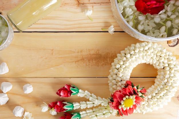 Жасмин и гирлянда белой розы на деревянной предпосылке. фестиваль сонгкран в таиланде. традиционный тайский.