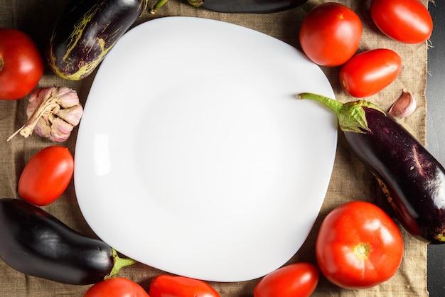 真ん中の空の白い皿と周りの野菜の平面図です。スペースをコピーします。