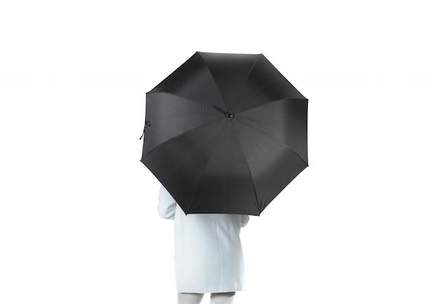 女性は黒い空白の傘を開いたまま後方に立つ