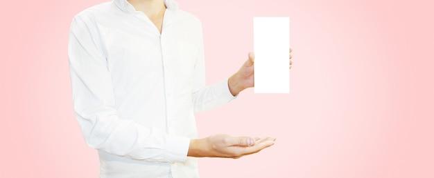 空白のパンフレットチラシを手で押し、白いシャツの男。