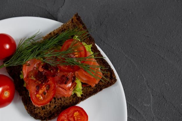 赤魚サーモンとマッシュアボカドのトースト、丸いトマトのスライスとディル