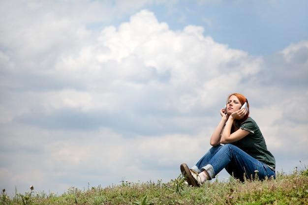 湖のほとりに座っているヘッドフォンを持つ若い女の子。