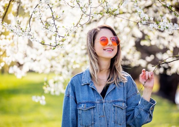 Молодая девушка в джинсовой куртке и солнцезащитных очках стоит возле цветущего дерева