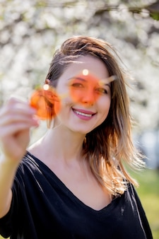 Молодая девушка в солнечных очках возле цветущего дерева