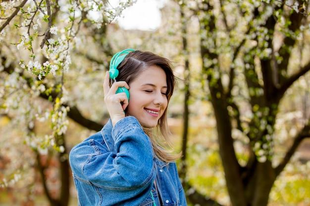 Девушка в джинсовой куртке и наушниках стоит возле цветущего дерева