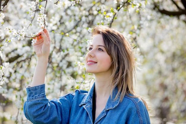 Девушка в джинсовой куртке возле цветущего дерева