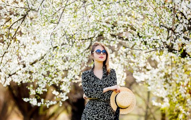 Молодая девушка в солнцезащитных очках и шляпе возле цветущего дерева