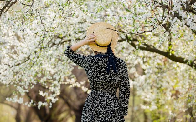Молодая девушка в шляпе возле цветущего дерева