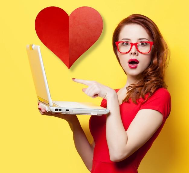 Удивленная рыжая девушка с ноутбуком и сердцем