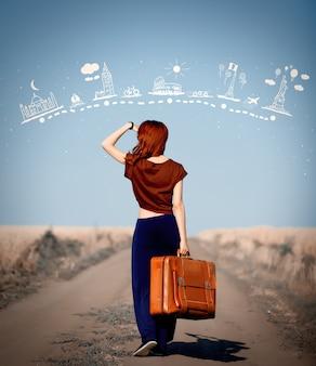 田舎道でスーツケースを持って赤毛の女の子