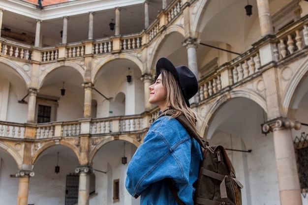古いお城のバックパックと帽子とデニムのジャケットの若い女性
