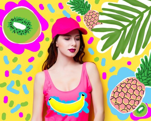 ピンクの水着とファッションキャップのエレガントなブルネットの女性。ピンクのビーチウェア、黄色の夏の背景に太陽を楽しんでいるサングラスでセクシーな女性