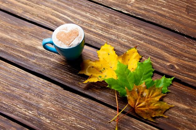 一杯のコーヒーと紅葉の素敵な茶色の木製の背景の写真