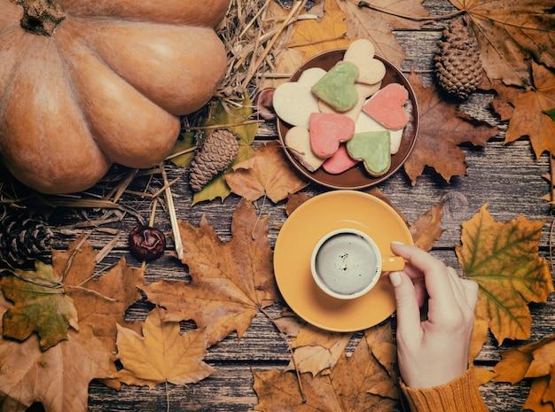 秋の背景にクッキーの近くのコーヒーを保持している女性。