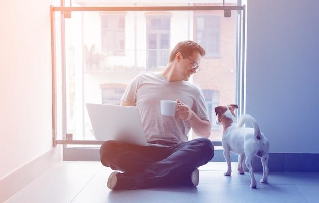 ラップトップコンピューターと一杯のコーヒーを使用してフリーランサー男