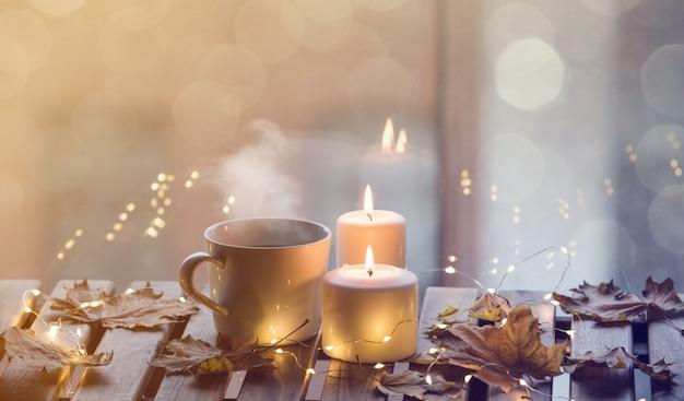カエデの葉の蝋燭の近くのコーヒーや紅茶の白いカップ