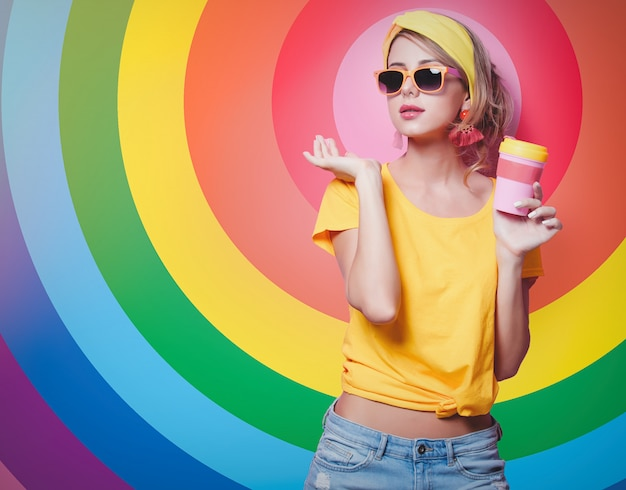 Девушка держит красную чашку кофе
