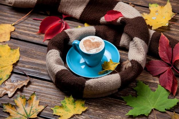 Листья осени, шарф и кофейная чашка на деревянном столе.
