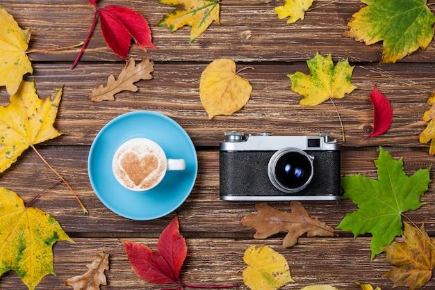 Листья осени, камера и кофейная чашка на деревянном столе.