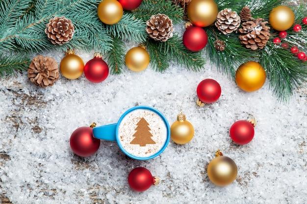 クリスマスツリーの形と人工の背景に松の枝のカプチーノ。