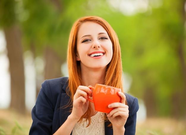 屋外でオレンジ色のカップと赤毛の女の子