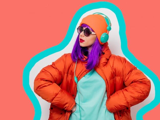 描かれた生きているサンゴ色の背景上のヘッドフォンを持つ若いスタイルの女の子。