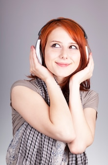 Молодая женщина прослушивания музыки с наушниками. портрет на сером фоне