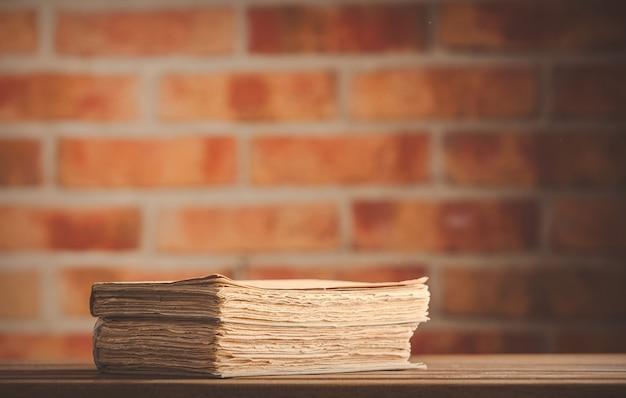 レンガの壁に木製のテーブルの上の古い本