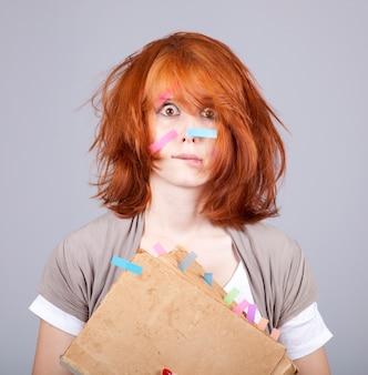 本と顔にメモを持つ赤毛の女性を驚かせた。