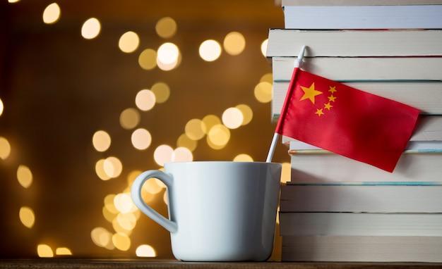本の近くの中国国旗と白いカップ