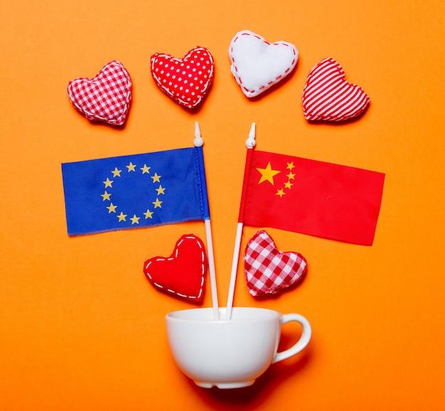 欧州連合と中国の国旗と白いカップとハートの形
