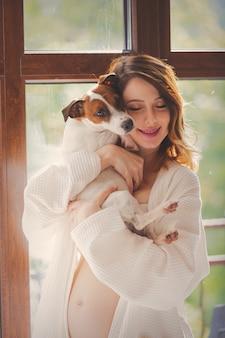 Молодая беременная женщина в нижнем белье с собакой