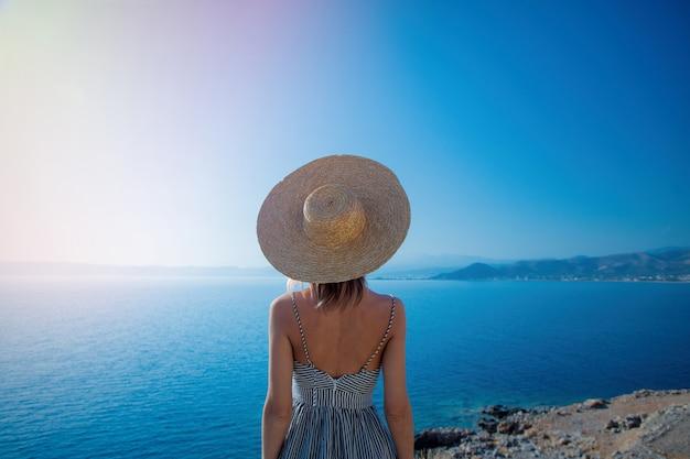 帽子と海の海岸線とドレスの女の子