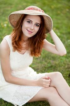 屋外の村で緑の芝生で赤毛の女の子。