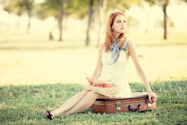 赤毛の女の子は屋外でバッグに座っています。