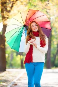 秋の屋外で傘を持つ赤いスカーフで十代の少女