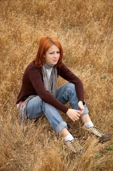 田舎で黄色い草の上に座って悲しい赤毛の女の子