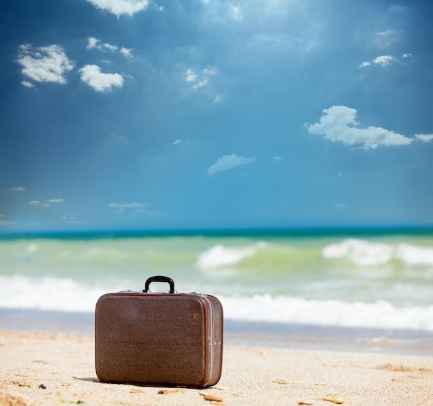 素晴らしい太陽が降り注ぐビーチの背景に美しい茶色のスーツケースの写真