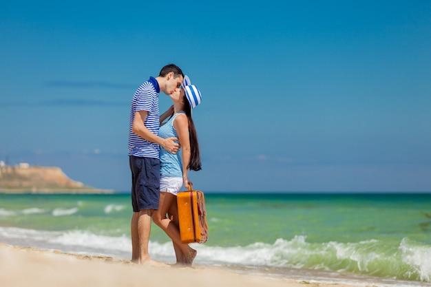 スーツケースと青い服の愛のカップルで
