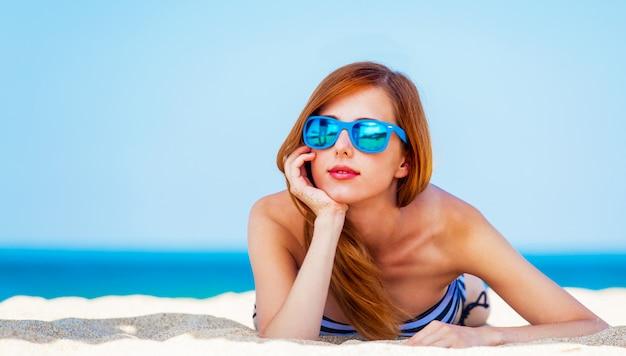 Рыжая девушка на пляже в весеннее время.