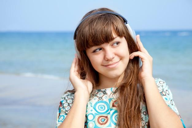 ビーチでヘッドフォンを持つ若い黒髪の女の子。