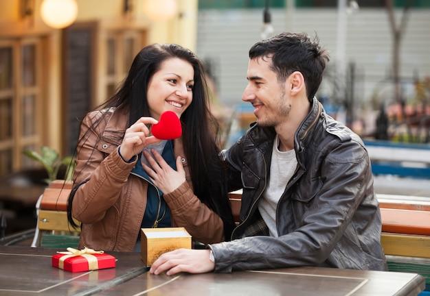 若い男がカフェで若い女の子に贈り物をすると彼らはキスをしています。